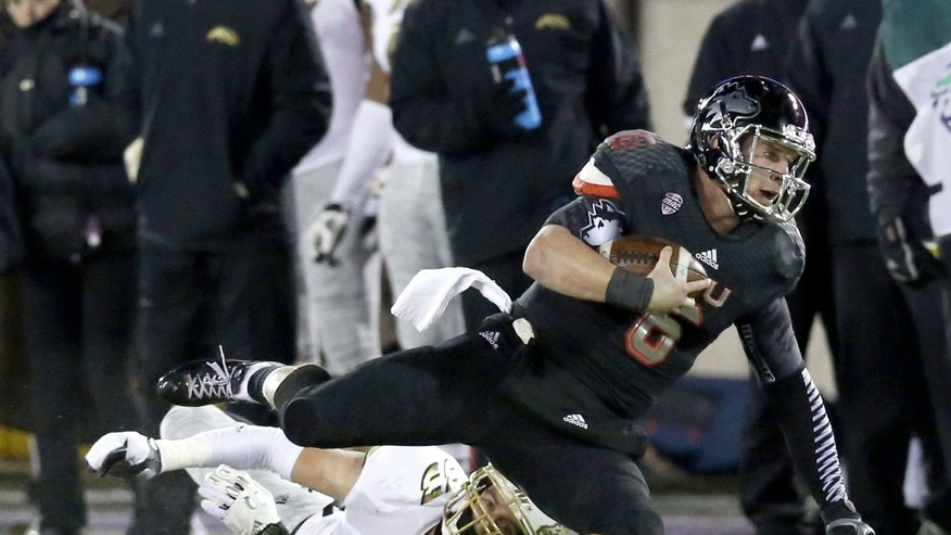 Northern Illinois quarterback Jordan Lynch carries the ball past Western Michigan safety Justin Currie during the second half of an NCAA football game Tuesday, Nov. 26, 2013, in DeKalb, Ill. (AP Photo/Charles Rex Arbogast)