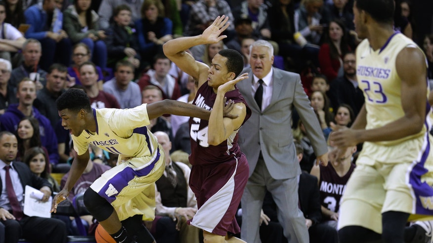 Washington guard Mike Anderson, left, is fouled by Montana's Chris Kemp in the second half of an NCAA college basketball game at the Alaska Airlines Arena on Tuesday, Nov. 26, 2013. (AP Photo/The Seattle Times, Lindsey Wasson)  SEATTLE OUT, USA TODAY OUT, MAGAZINES OUT, TELEVISION OUT, SALES OUT. MANDATORY CREDIT