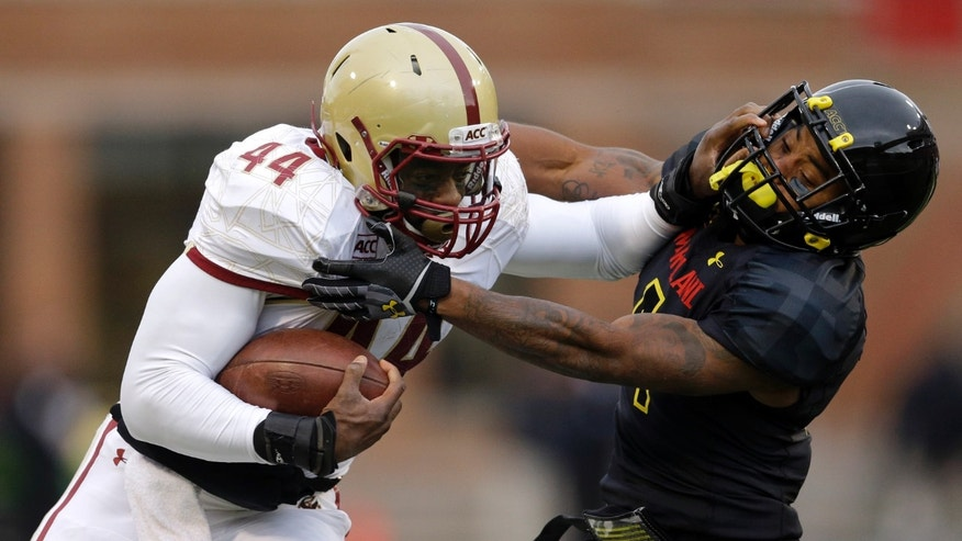 Boston College running back Andre Williams, left, pushes away Maryland defensive back William Likely while rushing the ball in the first half of an NCAA college football game in College Park, Md., Saturday, Nov. 23, 2013. (AP Photo/Patrick Semansky)