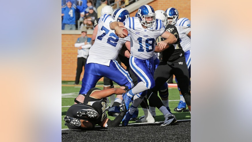 Duke quarterback Brandon Connette (18) runs past Wake Forest linebacker Marquel Lee (40) for a touchdown during the second half of an NCAA college football game in Winston-Salem, N.C., Saturday, Nov. 23, 2013. Duke won 28-21. (AP Photo/Chuck Burton)