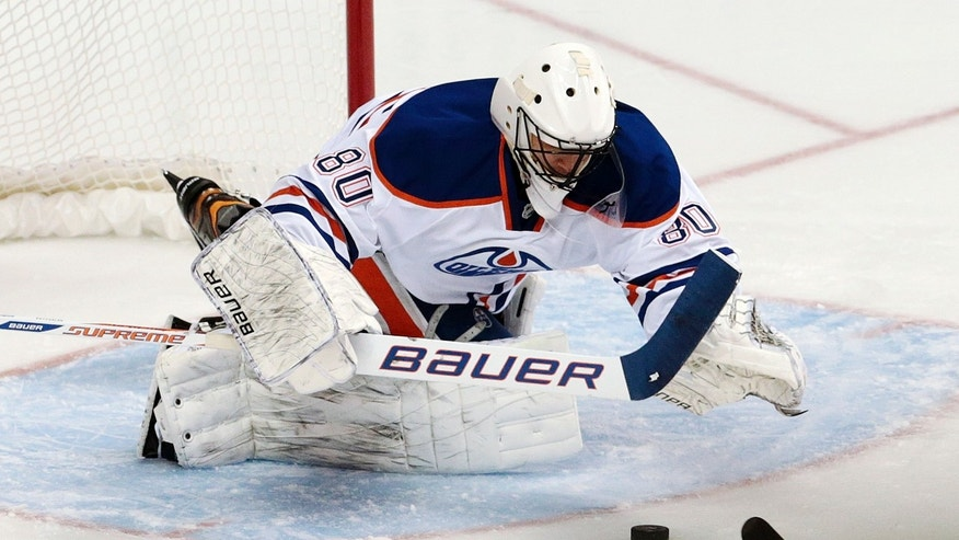 Edmonton Oilers goalie Ilya Bryzalov, of Russia, dives on a puck as he blocks a shot against the Nashville Predators in the second period of an NHL hockey game Thursday, Nov. 28, 2013, in Nashville, Tenn. (AP Photo/Mark Humphrey)
