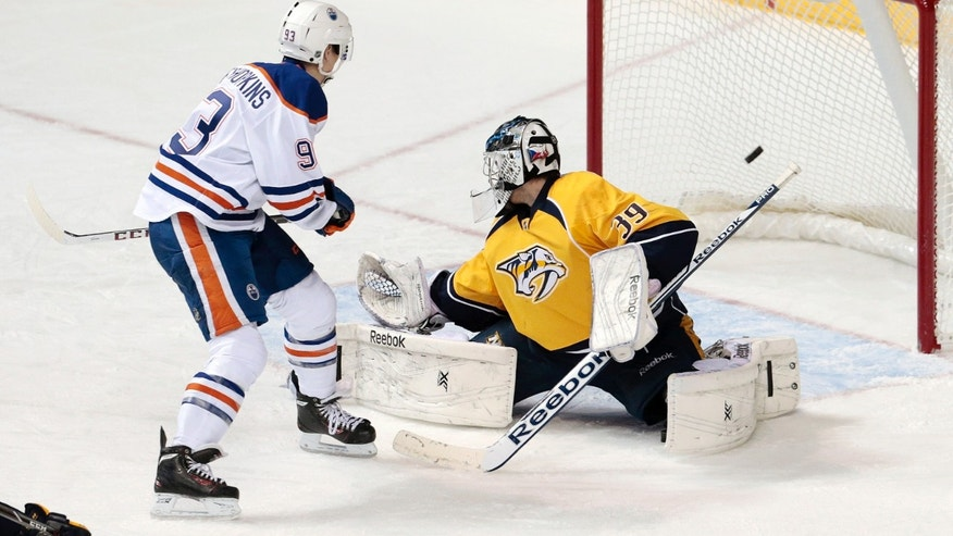 Edmonton Oilers forward Ryan Nugent-Hopkins, left, scores against Nashville Predators goalie Marek Mazanec (39), of Czech Republic, in the second period of an NHL hockey game Thursday, Nov. 28, 2013, in Nashville, Tenn. (AP Photo/Mark Humphrey)