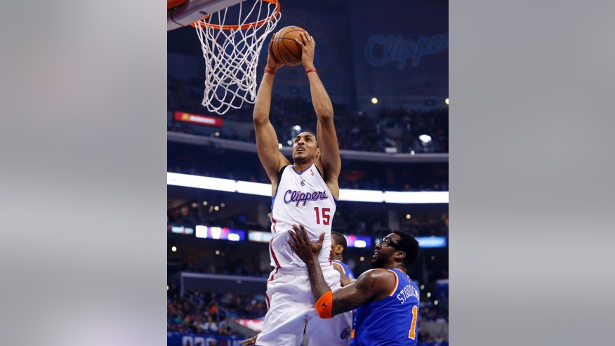 Los Angeles Clippers' Ryan Hollins, left, dunks the ball over New York Knicks' Amar'e Stoudemire during the first half of an NBA basketball game in Los Angeles, Wednesday, Nov. 27, 2013. (AP Photo/Danny Moloshok)