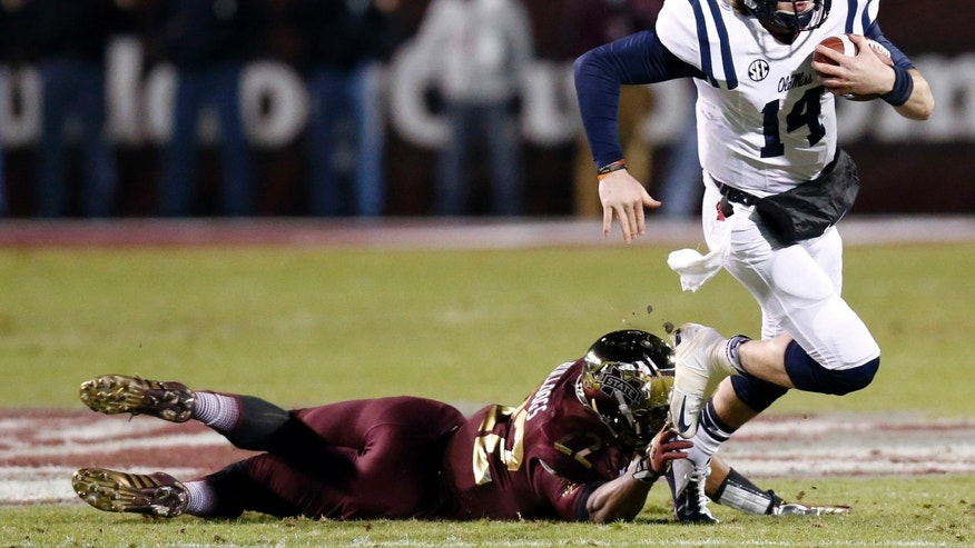 Mississippi State linebacker Matthew Wells (22) tackles Mississippi quarterback Bo Wallace (14) behinds the line of scrimmage during the first half of an NCAA college football game on Thursday, Nov. 28, 2013, in Starkville, Miss. (AP Photo/Rogelio V. Solis)