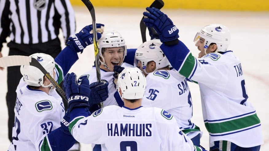 Vancouver Canucks' David Booth (facing camera) celebrates a goal against the Ottawa Senators with teammates during second-period NHL hockey game action in Ottawa, Ontario, Thursday, Nov. 28, 2013. The Canucks won 5-2. (AP Photo/The Canadian Press, Sean Kilpatrick)