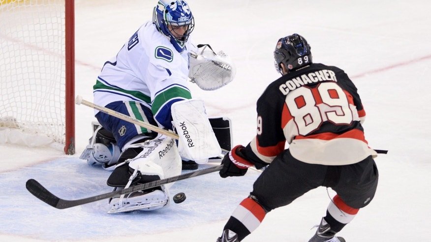 Ottawa Senators' Cory Conacher, right, comes up short on a goal-attempt against Vancouver Canucks' Roberto Luongo during third-period NHL hockey game action in Ottawa, Ontario, Thursday, Nov. 28, 2013. The Canucks won 5-2. (AP Photo/The Canadian Press, Sean Kilpatrick)