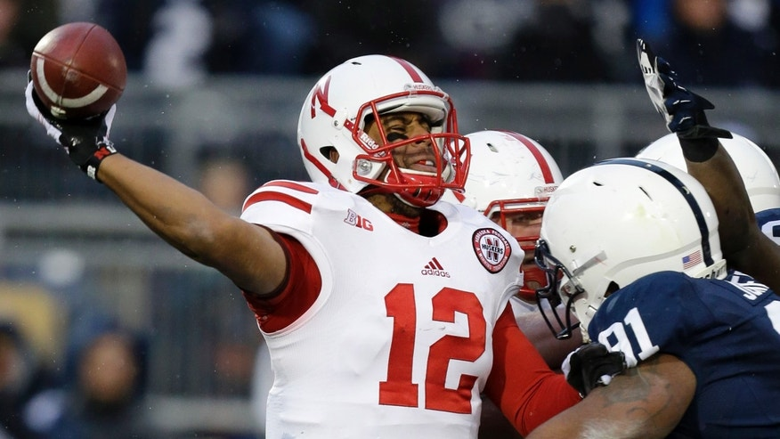 Nebraska quarterback Ron Kellogg III (12) pass under pressure from Penn State defensive tackle DaQuan Jones (91) during the second quarter of an NCAA college football game in State College, Pa., Saturday, Nov. 23, 2013. (AP Photo/Gene J. Puskar)