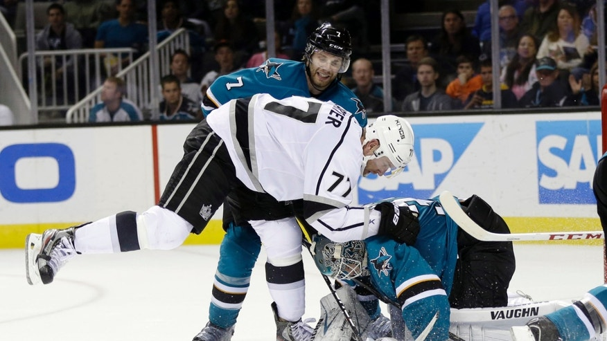 Los Angeles Kings' Jeff Carter (77) collides with San Jose Sharks goalie Antti Niemi, right, of Finland, and defenseman Brad Stuart (7) during the second period of an NHL hockey game Wednesday, Nov. 27, 2013, in San Jose, Calif. (AP Photo/Marcio Jose Sanchez)