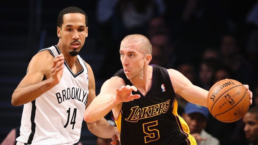 Los Angeles Lakers point guard Steve Blake (5) drives around Brooklyn Nets point guard Shaun Livingston (14) in the first quarter of an NBA basketball game at the Barclays Center, Wednesday, Nov. 27, 2013, in New York. (AP Photo/John Minchillo)
