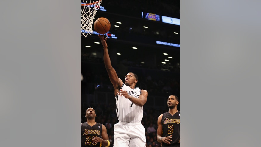 Brooklyn Nets shooting guard Joe Johnson (7) scores as Los Angeles Lakers shooting guard Jodie Meeks (20) and power forward Shawne Williams (3) look on in the second quarter of an NBA basketball game at the Barclays Center, Wednesday, Nov. 27, 2013, in New York. (AP Photo/John Minchillo)