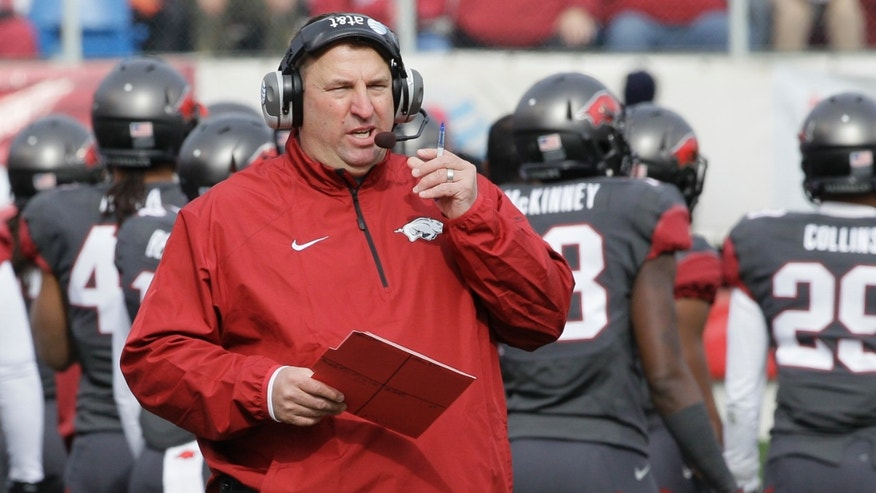 Arkansas coach Bret Bielema talks on his headset in the first half of an NCAA college football game against Mississippi State in Little Rock, Ark., Saturday, Nov. 23, 2013. (AP Photo/Danny Johnston)