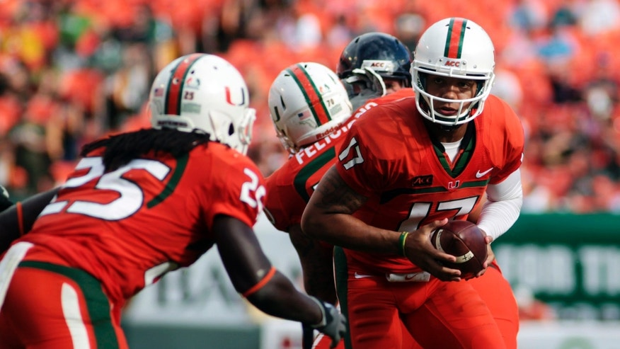Miami's Stephen Morris (17) hands off to Dallas Crawford (25) during the second half of an NCAA college football game against Virginia in Miami Gardens, Fla., Saturday, Nov. 23, 2013.  (AP Photo/J Pat Carter)