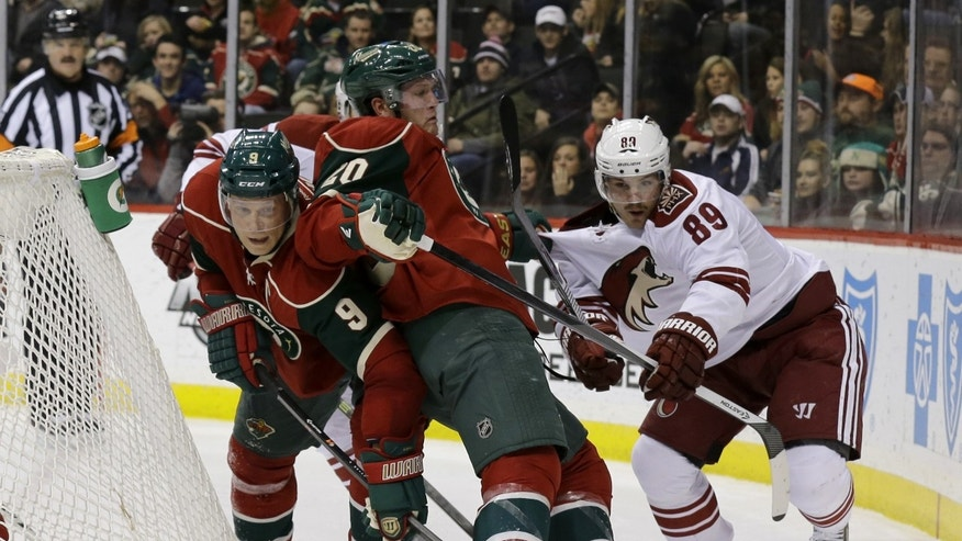 Minnesota Wild defenseman Ryan Suter (20) gets caught between Wild center Mikko Koivu (9), of Finland, and Phoenix Coyotes left wing Mikkel Boedker (89), of Denmark, as they chase the puck during the second period of an NHL hockey game in St. Paul, Minn., Wednesday, Nov. 27, 2013. (AP Photo/Ann Heisenfelt)
