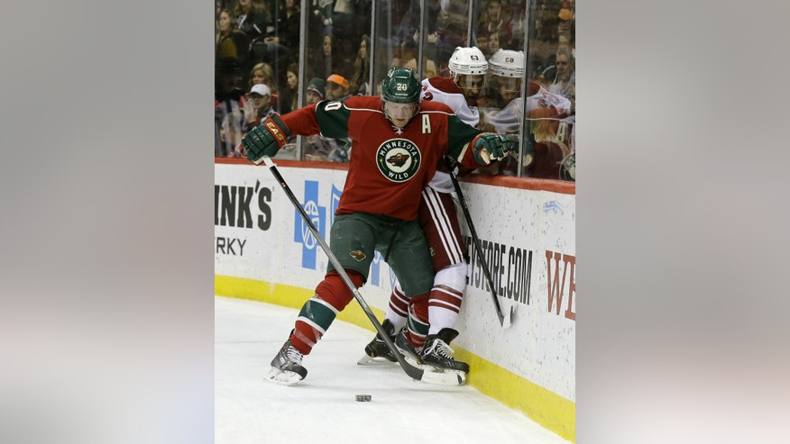 Minnesota Wild defenseman Ryan Suter (20) pins Phoenix Coyotes center Mike Ribeiro (63) against the boards as they chase the puck during the second period of an NHL hockey game in St. Paul, Minn., Wednesday, Nov. 27, 2013. (AP Photo/Ann Heisenfelt)