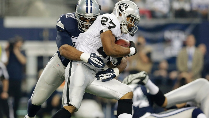 Oakland Raiders running back Rashad Jennings (27) is tackled by Dallas Cowboys defensive tackle Jason Hatcher (97) during the first half of an NFL football game, Thursday, Nov. 28, 2013, in Arlington, Texas.  (AP Photo/LM Otero)