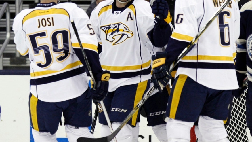 Nashville Predators' Mike Fisher, center, celebrates his goal against the Columbus Blue Jackets with teammates Roman Josi (59), of Switzerland, and Shea Weber (6) in the second period of an NHL hockey game in Columbus, Ohio, Wednesday, Nov. 27, 2013. (AP Photo/Paul Vernon)