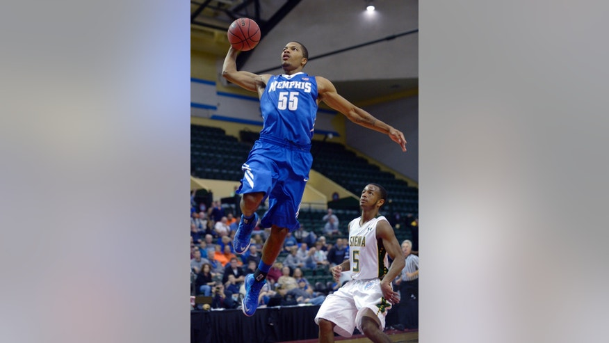 Memphis guard Geron Johnson (55) goes up to dunk the ball in front of Siena guard Evan Hymes (5) during the first half of an NCAA college basketball game in Kissimmee, Fla., Thursday, Nov. 28, 2013. (AP Photo/Phelan M. Ebenhack)