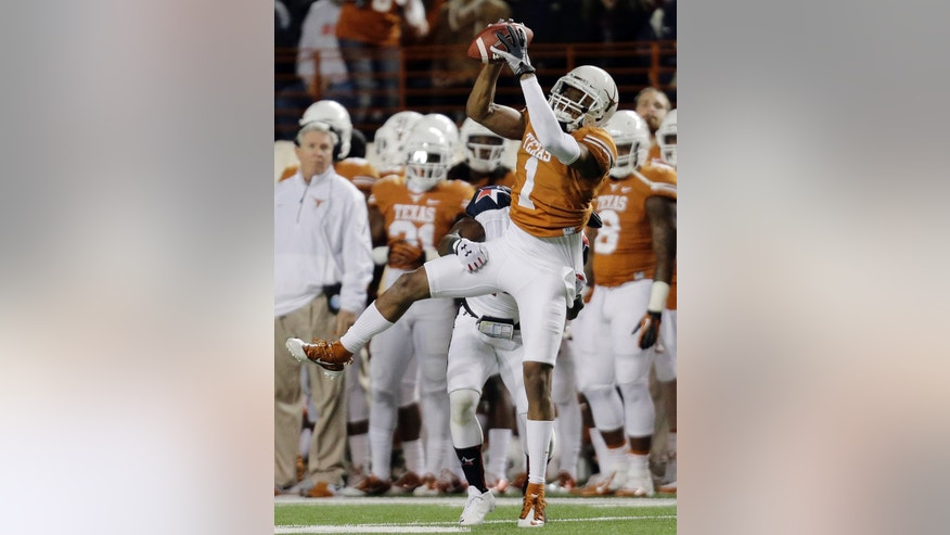 Texas' Mike Davis (1) catches a pass for a first down in front of Texas Tech's Bruce Jones during the first half of an NCAA college football game Thursday, Nov. 28, 2013, in Austin, Texas. (AP Photo/Eric Gay)