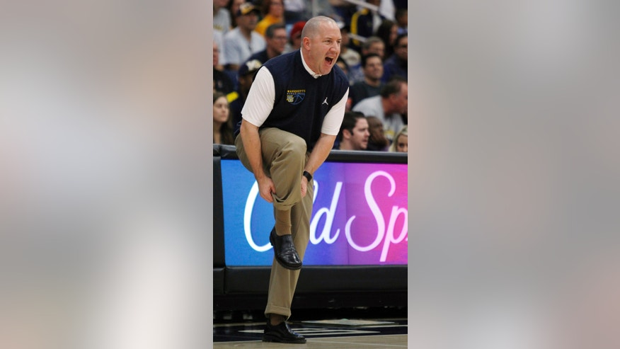 Marquette head coach Buzz Williams adjusts his socks while calling out a defense for his team against Cal State Fullerton in the first half of an NCAA college basketball game at the Wooden Legacy tournament Thursday, Nov. 28, 2013, in Fullerton, Calif. (AP Photo/Alex Gallardo)