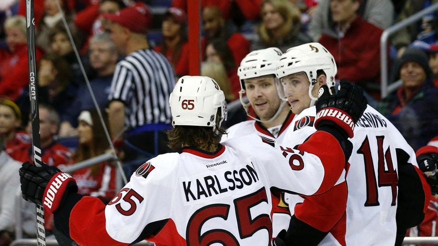 Ottawa Senators defenseman Erik Karlsson (65), from Sweden, center Zack Smith (15) and left wing Colin Greening (14) celebrate Greening's goal in the second period of an NHL hockey game against the Washington Capitals, Wednesday, Nov. 27, 2013, in Washington. (AP Photo/Alex Brandon)