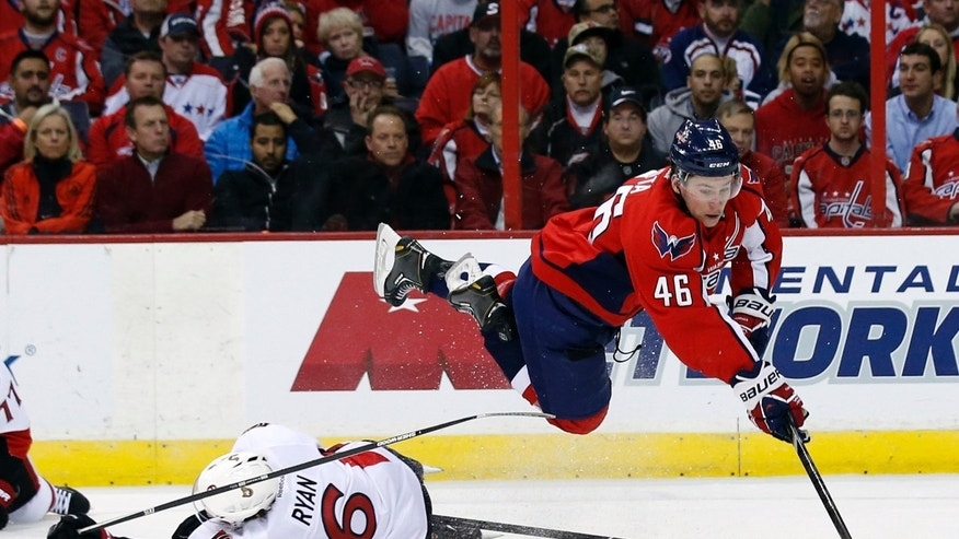 Washington Capitals center Michael Latta (46) dives over Ottawa Senators right wing Bobby Ryan (6) for the puck, to pass to right wing Eric Fehr, who scored on the play giving Latta an assist, during the first period of an NHL hockey game, Wednesday, Nov. 27, 2013, in Washington. (AP Photo/Alex Brandon)
