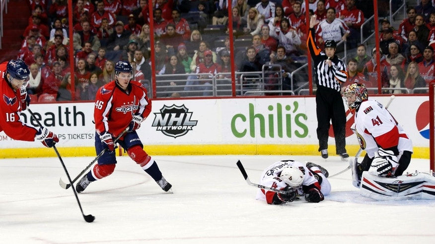 Washington Capitals right wing Eric Fehr (16) shoots for a goal past Ottawa Senators defenseman Chris Phillips (4) and goalie Craig Anderson (41) in the first period of an NHL hockey game, Wednesday, Nov. 27, 2013, in Washington. (AP Photo/Alex Brandon)