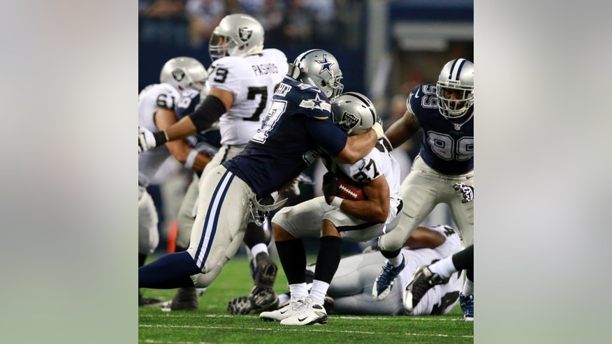 Oakland Raiders running back Rashad Jennings (27) is tackled by Dallas Cowboys defensive tackle Jason Hatcher during the second half of an NFL football game Thursday, Nov. 28, 2013, in Arlington, Texas. (AP Photo/The Waco Tribune-Herald, Jose Yau)