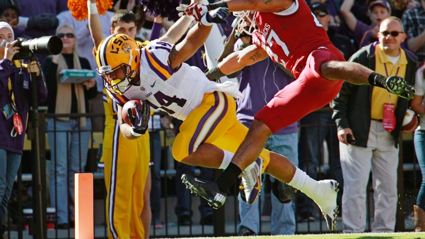 LSU running back Terrence Magee (14) gets into the end zone in front of Arkansas safety Alan Turner (27) for a touchdown in the first half of an NCAA college football game in Baton Rouge, La., Friday, Nov. 29, 2013. (AP Photo/Bill Haber)