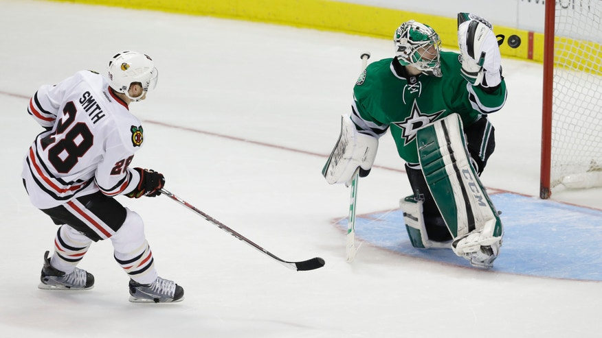 Chicago Blackhawks right wing Ben Smith (28) shoots the puck past Dallas Stars goalie Kari Lehtonen (32) in the shootout of an NHL hockey game Friday, Nov. 29, 2013, in Dallas. The Blackhawks won 2-1. (AP Photo/LM Otero)
