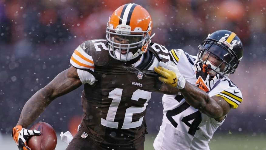Cleveland Browns wide receiver Josh Gordon (12) is tackled by Pittsburgh Steelers cornerback Ike Taylor (24) after a catch in the fourth quarter of an NFL football game Sunday, Nov. 24, 2013, in Cleveland. The Steelers won 27-11. (AP Photo/Tony Dejak)