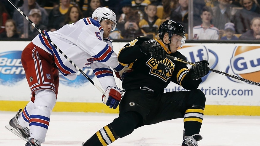New York Rangers defenseman Dan Girardi (5) knocks down Boston Bruins' Carl Soderberg, of Sweden, during the second period of an NHL hockey game in Boston Friday, Nov. 29, 2013. (AP Photo/Winslow Townson)