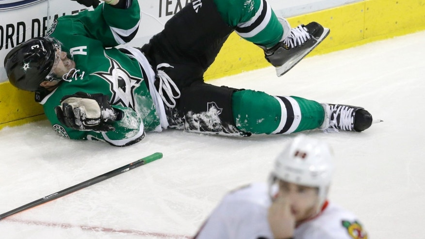 Dallas Stars defenseman Stephane Robidas (3) lies on the ice in pain after injuring his leg during the second period of an NHL hockey game against the Chicago Blackhawks on Friday, Nov. 29, 2013, in Dallas. (AP Photo/LM Otero)