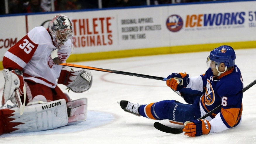 Detroit Red Wings goalie Jimmy Howard (35) deflects a shot by New York Islanders center Peter Regin, of Denmark, during the second period of an NHL hockey game Friday, Nov. 29, 2013, in Uniondale, N.Y. (AP Photo/Julio Cortez)