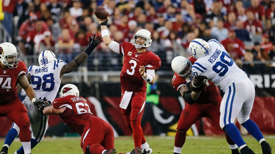 Arizona Cardinals quarterback Carson Palmer (3) throws under pressure from Indianapolis Colts' Robert Mathis (98) and Cory Redding (90) as Cardinals' Daryn Colledge (71) and Lyle Sendlein (63) block during the second half of an NFL football game, Sunday, Nov. 24, 2013, in Glendale, Ariz. (AP Photo/Matt York)