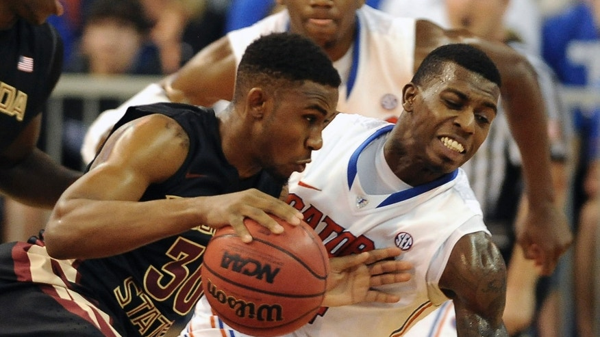 Florida State guard Ian Miller (30) drives through Florida forward Casey Prather (24) during the first half of an NCAA college basketball game on Friday, Nov. 29, 2013, in Gainesville, Fla. (AP Photo/Phil Sandlin)