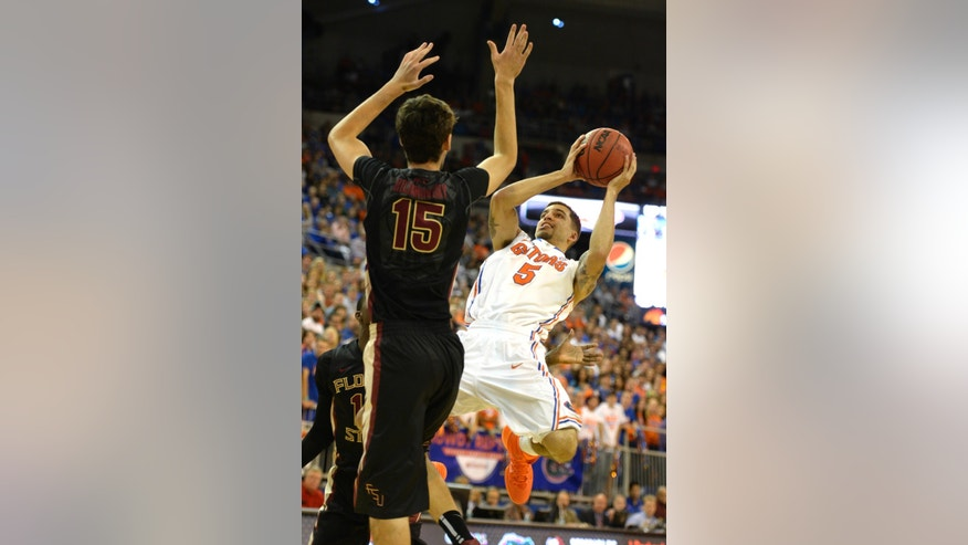 Florida guard Scottie Wilbekin (5) shoots as he is pressured by Florida State center Boris Bojanovsky (15) during the first half of an NCAA college basketball game on Friday, Nov. 29, 2013, in Gainesville, Fla. (AP Photo/Phil Sandlin)