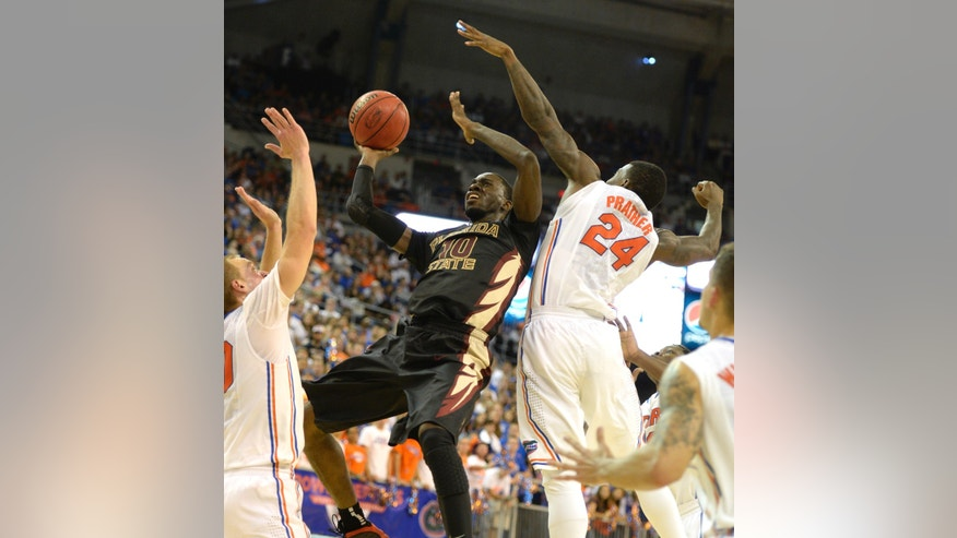 Florida State forward Okaro White (10) is blocked from making two points by Florida forwards Jacob Kurtz (30) and Casey Prather (24) During the second half of an NCAA college basketball game on Friday, Nov. 29, 2013, in Gainesville, Fla. (AP Photo/Phil Sandlin)
