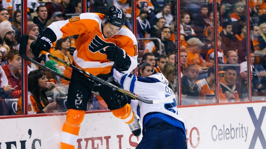 Philadelphia Flyers' Brayden Schenn, left, gets checked by Winnipeg Jets' Grant Clitsome, right, during the second period of an NHL hockey game, Friday, Nov. 29, 2013, in Philadelphia. (AP Photo/Chris Szagola)