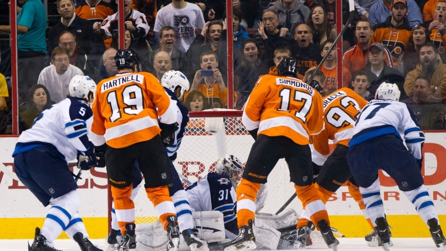 Winnipeg Jets' Ondrej Pavelec, center, stops the shot by Philadelphia Flyers' Jakub Voracek, of Czech Republic, second from the left, with Winnipeg Jets' Mark Stuart, left, Dustin Byfuglien, third from the left, and James Wright, right, along with Philadelphia Flyers' Scott Hartnell, second from the left, and Wayne Simmonds, third from the right, during the first period of an NHL hockey game, Friday, Nov. 29, 2013, in Philadelphia.  (AP Photo/Chris Szagola)