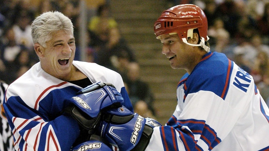 FILE - In a Nov. 6, 2004 file photo Rick Vaive, left, laughs as he grapples with  Mike Krushelnyski during the third period of the Hockey 2004 Legends Classic in Toronto. Ten former National Hockey League players, including former Toronto Maple Leafs' captain Vaive, claimed in a class-action lawsuit that the league hasn't done enough to protect players from concussions.  (AP Photo/The Canadian Press, Aaron Harris, file )