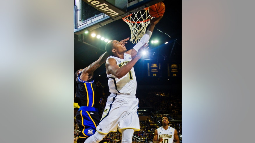 Michigan forward Glenn Robinson III (1) goes up to the basket in the second half of an NCAA college basketball game against Coppin State at Crisler Center in Ann Arbor, Mich., Friday, Nov. 29, 2013. Michigan won 87-45. (AP Photo/Tony Ding)