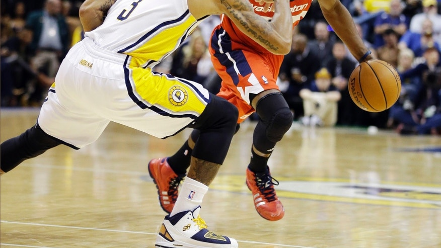 Washington Wizards' John Wall, right, drives to the basket against Indiana Pacers' George Hill (3) during the first half of an NBA basketball game Friday, Nov. 29, 2013, in Indianapolis. (AP Photo/Darron Cummings)