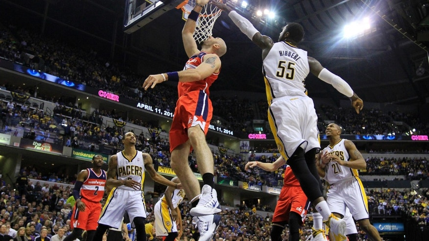 Washington Wizards' Marcin Gortat, left, puts up a shot against Indiana Pacers' Roy Hibbert (55) during the first half of an NBA basketball game Friday, Nov. 29, 2013, in Indianapolis. (AP Photo/Darron Cummings)