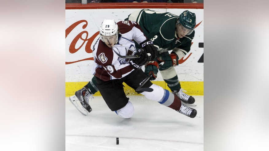 Colorado Avalanche center Nathan MacKinnon (29) and Minnesota Wild center Charlie Coyle, right, tangle as they chase the puck during the first period of an NHL hockey game in St. Paul, Minn., Friday, Nov. 29, 2013. (AP Photo/Ann Heisenfelt)