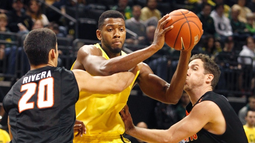 Pacific's Ross Rivera, left, and Trevin Harris, right, try to trap Oregon's Mike Moser during the second half of an NCAA collage basketball game in Eugene, Ore., on Friday, Nov. 29, 2013. (AP Photo/Chris Pietsch)