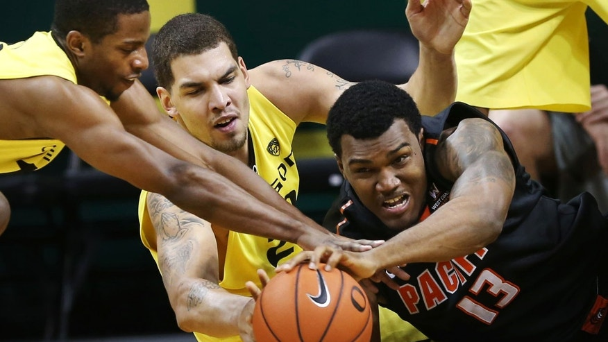 Oregon's Johnathan Loyd, left, and Waverly Austin, center, battle Pacific's Khalil Kelly for a loose ball during the second half of an NCAA collage basketball game in Eugene, Ore., on Friday, Nov. 29, 2013. (AP Photo/Chris Pietsch)