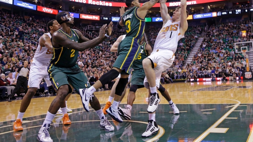 Phoenix Suns' Goran Dragic, right, of Slovenia, drives to the basket as Utah Jazz's Trey Burke (3) defends while teammate Utah Jazz's Marvin Williams (2) watches during the first quarter during an NBA basketball game Friday, Nov. 29, 2013, in Salt Lake City. (AP Photo/Rick Bowmer)