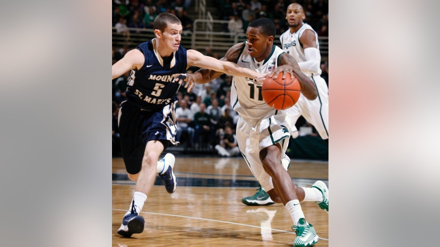 Michigan State's Keith Appling (11) drives against Mount St. Mary's Liam McManimon (5) during the first half of an NCAA college basketball game, Friday, Nov. 29, 2013, in East Lansing, Mich. Michigan State won 98-65. (AP Photo/Al Goldis)