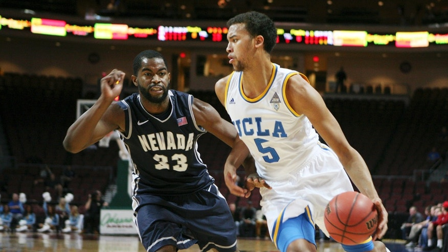 UCLA's Kyle Anderson, right, drives the ball past Nevada's Ronnie Stevens Jr. in the first half of the Las Vegas Invitational NCAA college basketball tournament Thursday, Nov. 28, 2013, in Las Vegas. (AP Photo/Ronda Churchill)