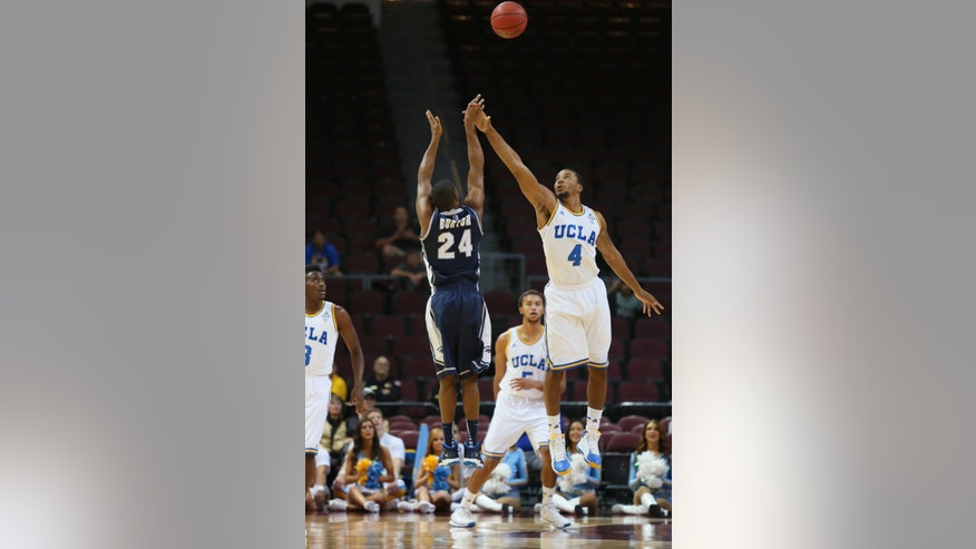 Nevada guard Deonte Burton (24) goes up to shoot as UCLA guard Norman Powell (4) attempts a block in the first half of the Las Vegas Invitational NCAA college basketball tournament on Thursday, Nov. 28, 2013, in Las Vegas. (AP Photo/Ronda Churchill)